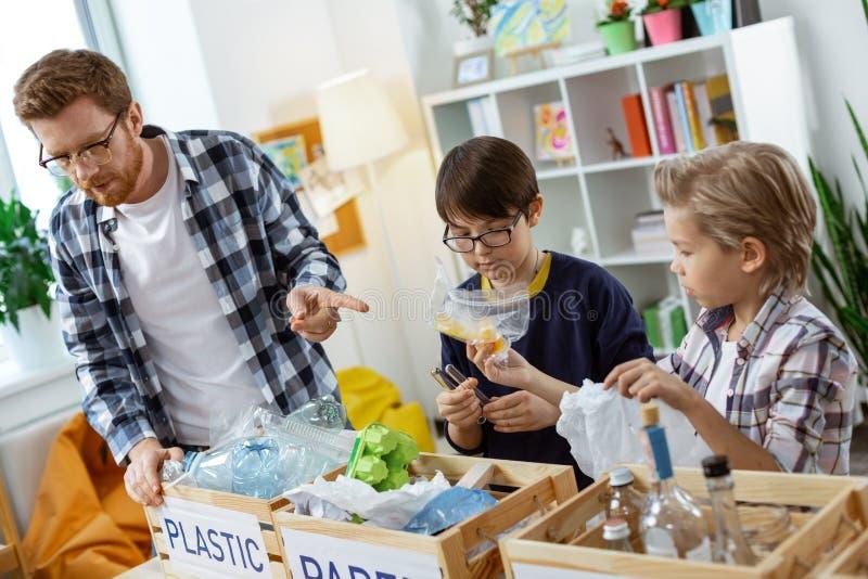 Crianças curiosas atentas que classificam para fora tipos diferentes do lixo fotografia de stock royalty free
