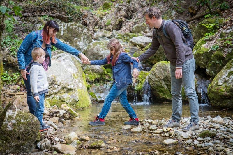 Crianças da ajuda da mamã e do paizinho para cruzar o córrego da montanha fotos de stock royalty free
