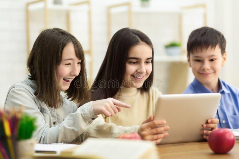 Crianças da escola com o tablet pc que tem o divertimento na ruptura foto de stock royalty free