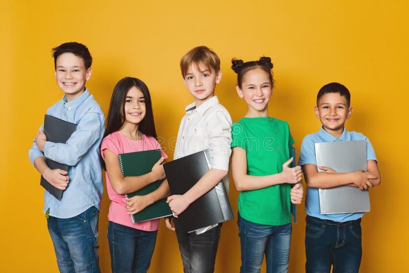 Crianças da escola com os cadernos sobre o fundo amarelo imagem de stock