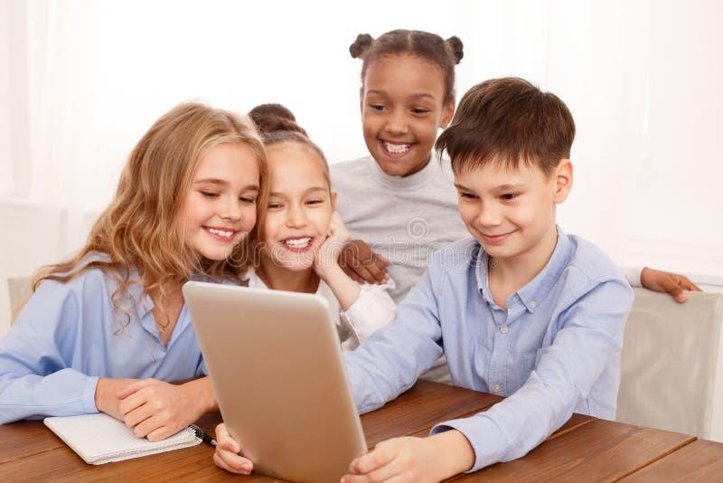 Crianças da escola com a tabuleta na ruptura na sala de aula foto de stock