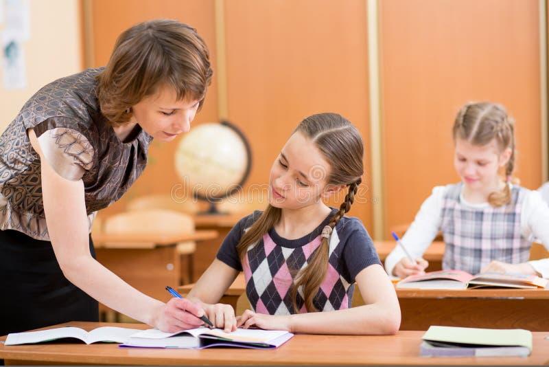 Crianças da escola e trabalho do professor na lição fotografia de stock
