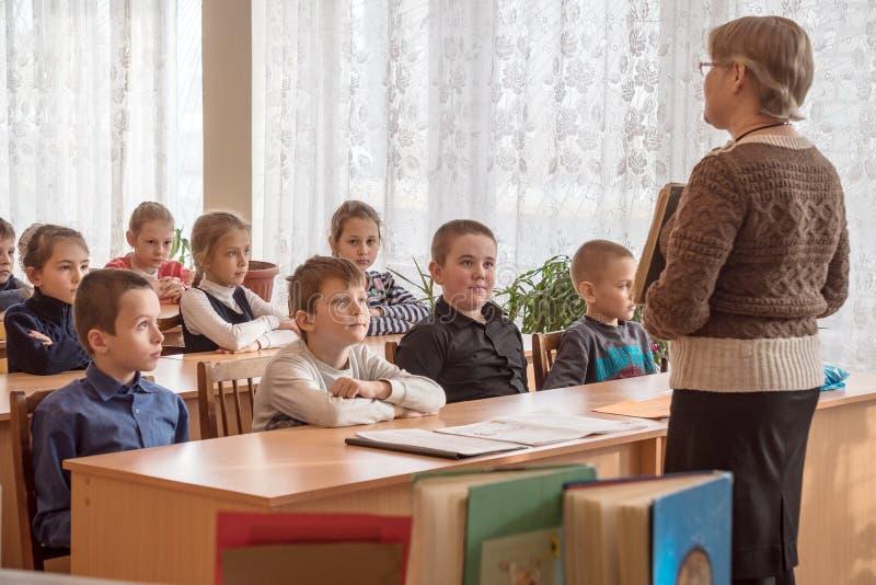 Crianças da escola na sala de aula com professor foto de stock