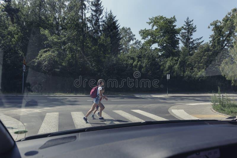 Crianças da escola no cruzamento pedestre, vista do interior do carro imagem de stock royalty free