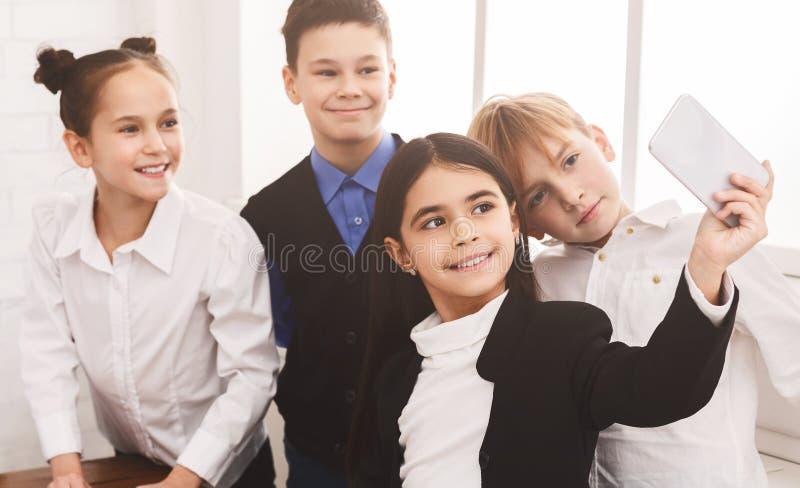 Crianças da escola que tomam o selfie no smartphone no corredor foto de stock royalty free