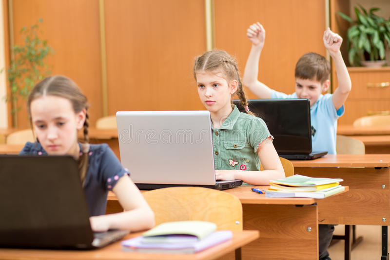 Crianças da escola que usam o portátil na lição foto de stock royalty free