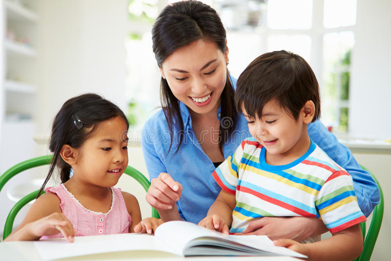 Crianças de ajuda da mãe com trabalhos de casa imagem de stock