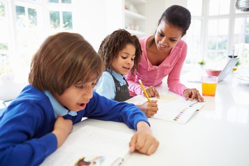 Crianças de ajuda da mãe com trabalhos de casa na cozinha fotos de stock royalty free