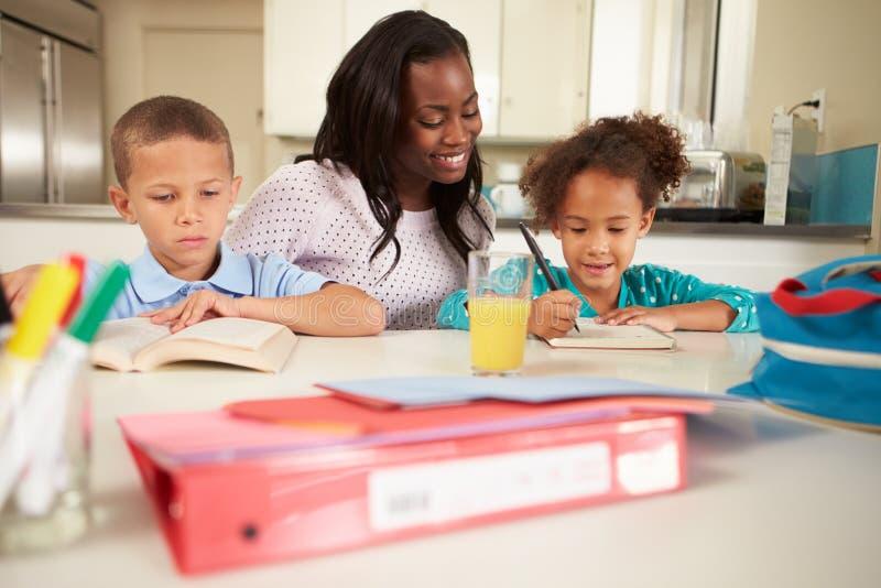 Crianças de ajuda da mãe com trabalhos de casa na tabela fotografia de stock royalty free