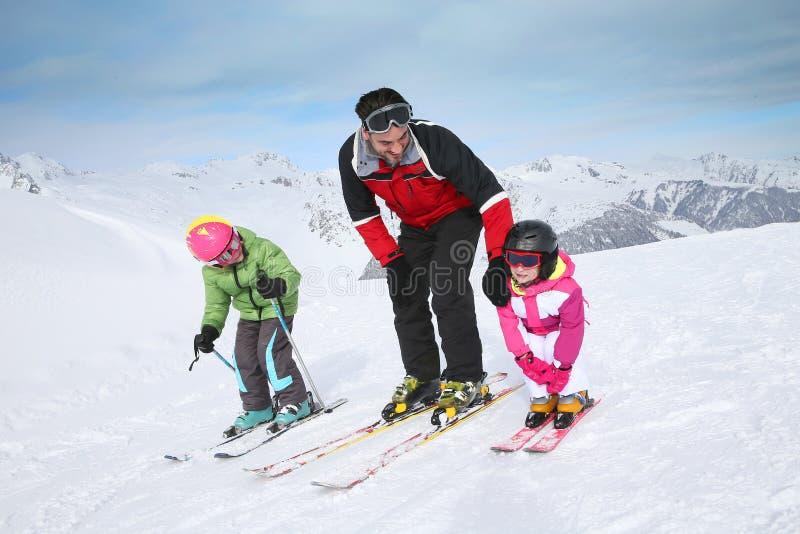 Crianças de ensino do instrutor do esqui esqui foto de stock royalty free