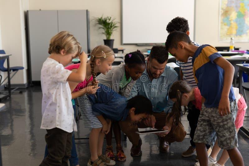 Crianças de ensino do professor masculino na tabuleta digital na sala de aula imagens de stock royalty free