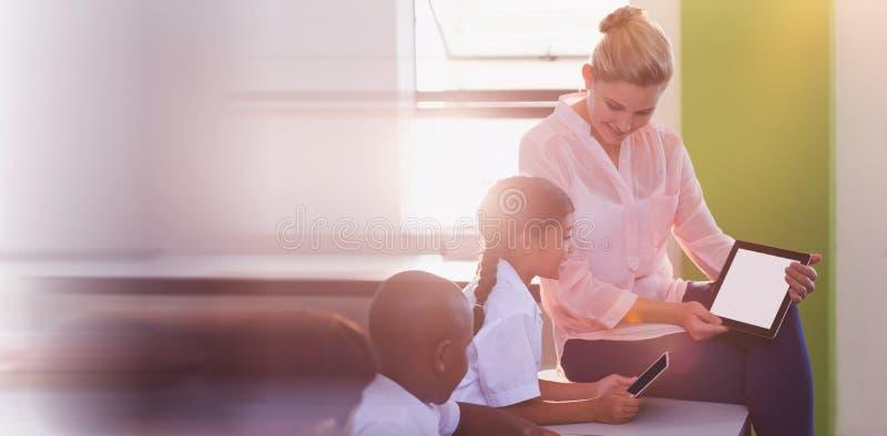 Crianças de ensino do professor na tabuleta digital fotografia de stock royalty free