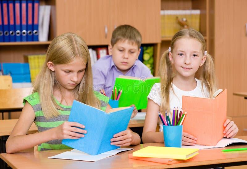 Crianças de escola primária nos livros de leitura da sala de aula imagens de stock royalty free
