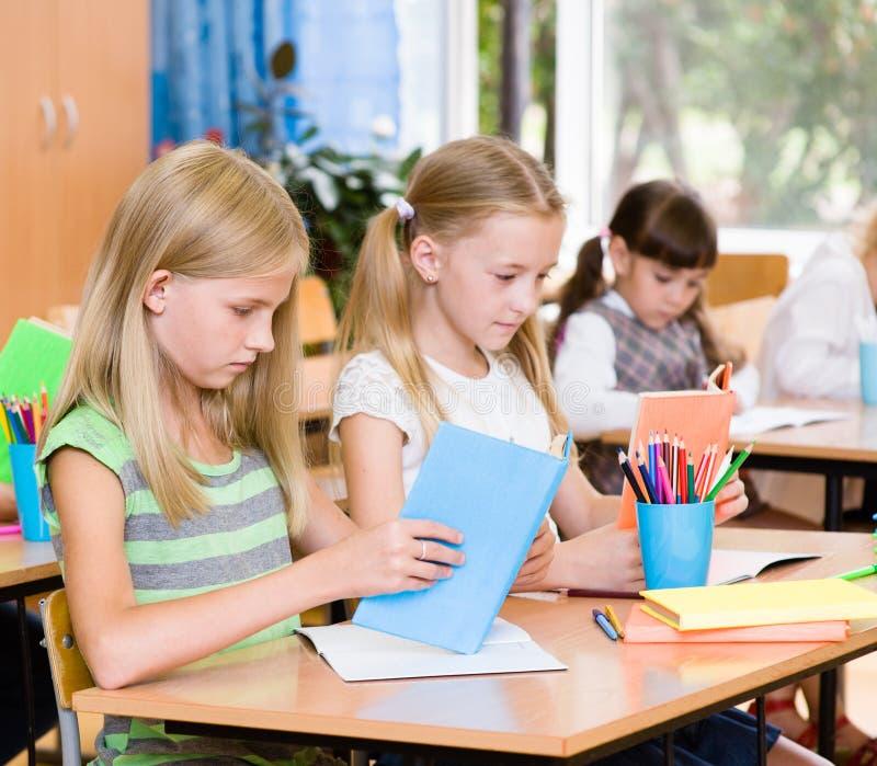 Crianças de escola primária nos livros de leitura da sala de aula fotografia de stock royalty free