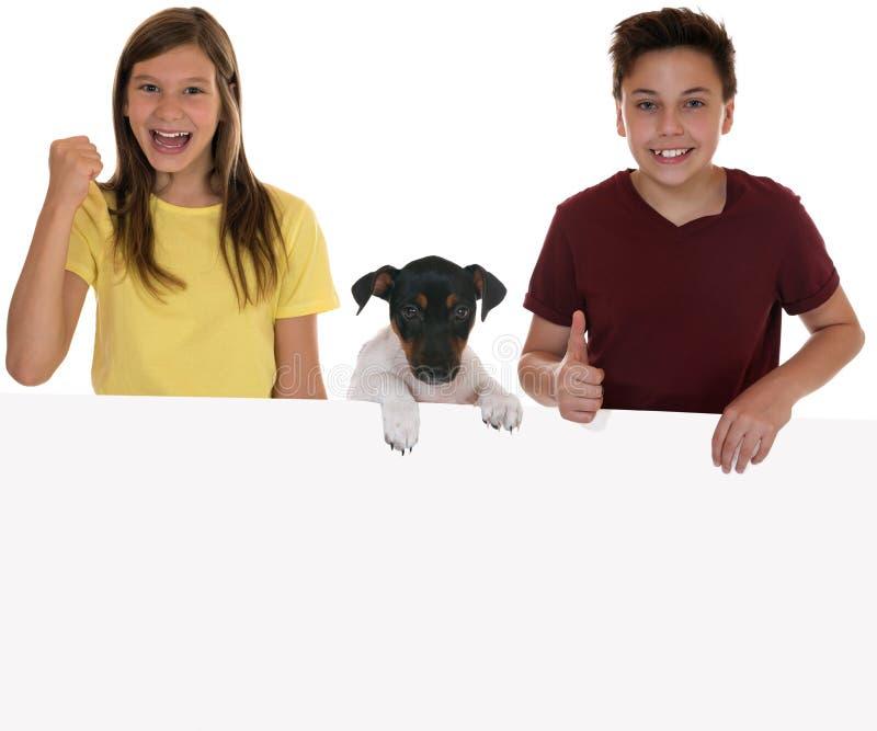 Crianças de sorriso com uma bandeira vazia, copyspace e um cão de cachorrinho foto de stock royalty free