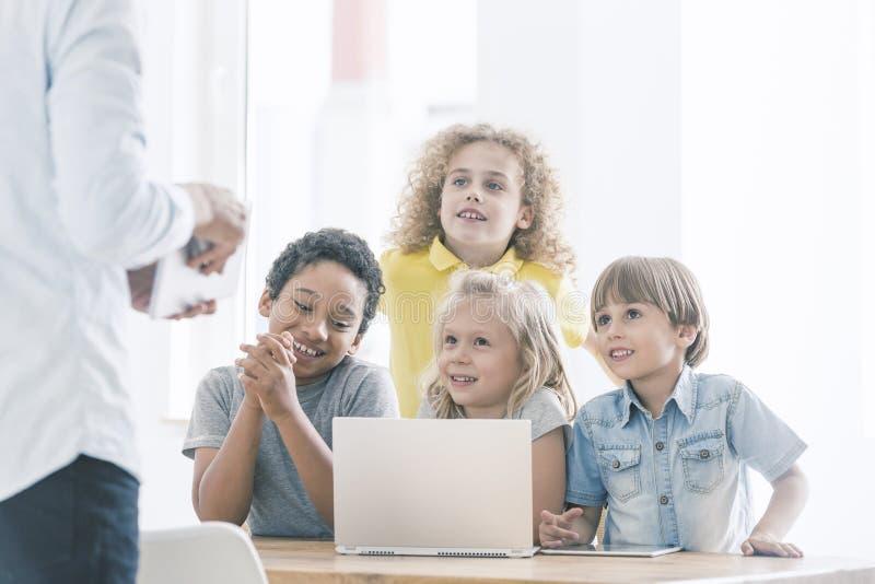 Crianças de sorriso durante classes de programação foto de stock royalty free