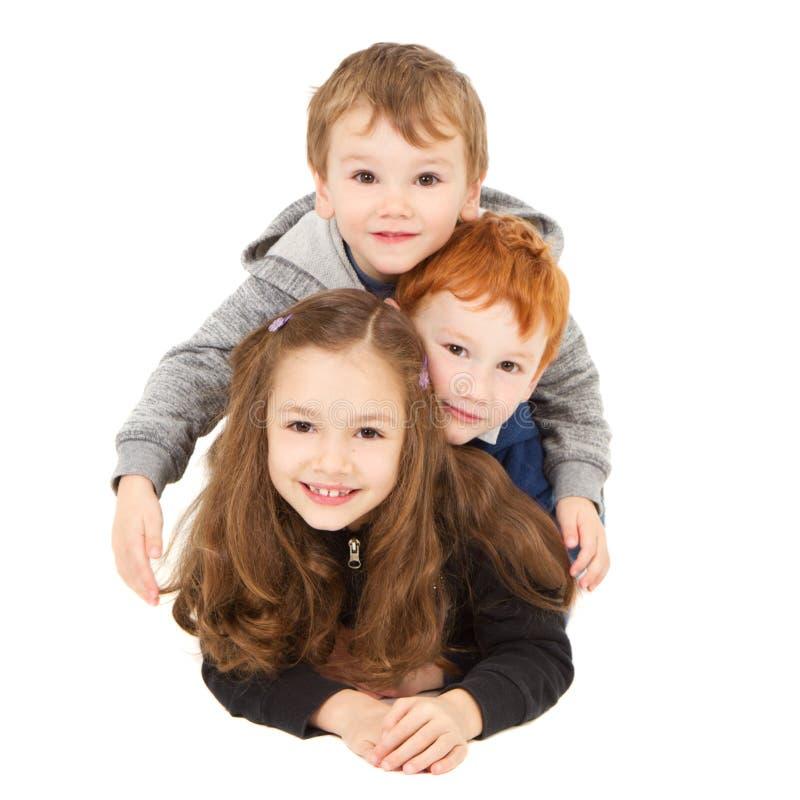 Crianças de sorriso felizes que colocam na pilha fotos de stock royalty free