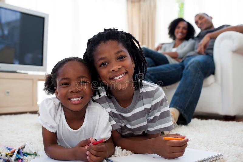 Crianças de sorriso que desenham o encontro no assoalho imagem de stock