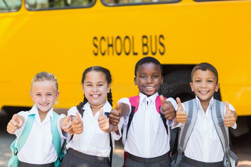 Crianças de sorriso que mostram os polegares acima na frente do ônibus escolar imagem de stock royalty free