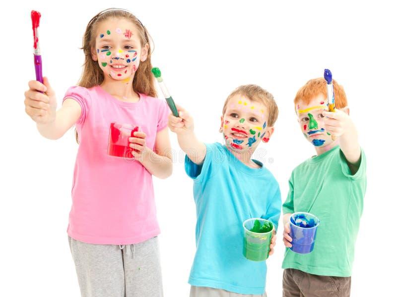 Crianças desarrumado de sorriso com escovas de pintura fotografia de stock