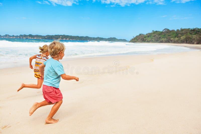 Crianças descalças felizes que correm com divertimento na caminhada da praia fotos de stock