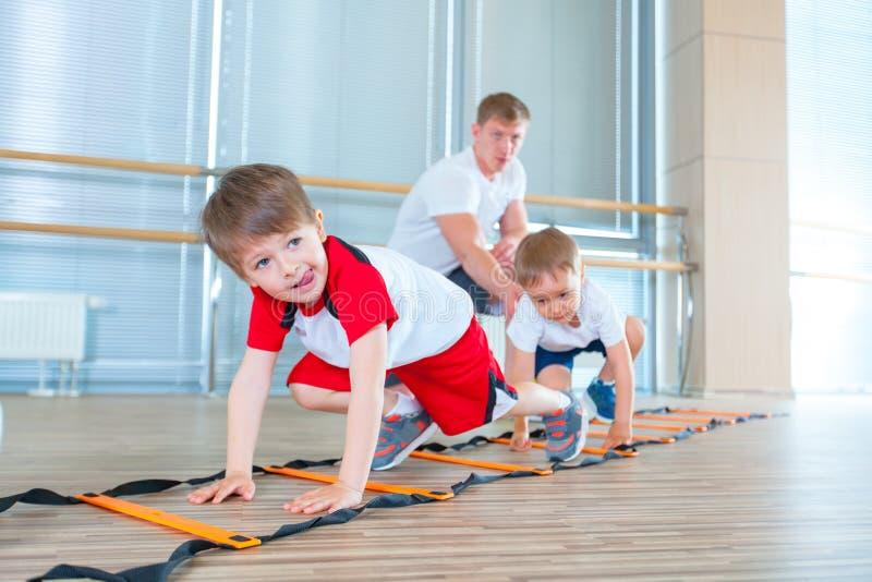 Crianças desportivas felizes no gym Exercícios das crianças fotos de stock