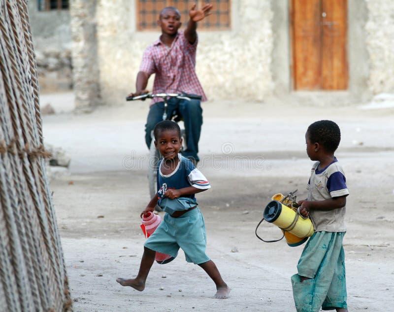 Crianças do africano negro que jogam na aldeia piscatória da rua fotos de stock