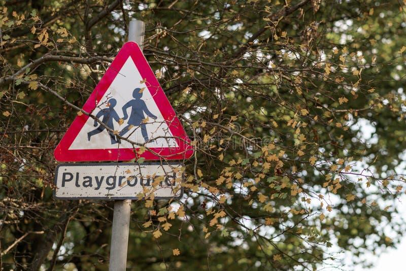 Crianças do campo de jogos que cruzam o sinal de estrada encontrado no Reino Unido com a beira vermelha brilhante clássica Dispar imagens de stock