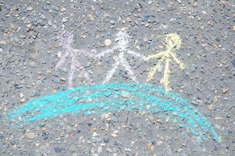 Crianças do globo pintadas com gizes no asfalto, dia internacional da amizade, figura sinal esboçado na terra imagem de stock