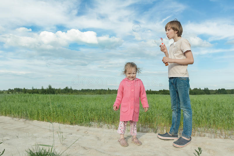 Crianças do irmão que têm o divertimento que compartilha de bolhas de sabão no campo verde da aveia do verão imagens de stock