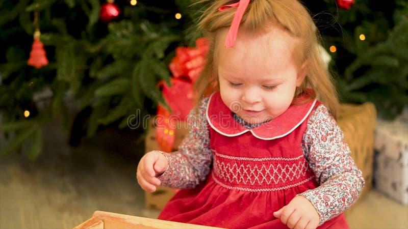 Crianças do Natal Criança pequena bonito perto da árvore Crianças do Natal Menina que joga com os brinquedos perto da árvore de N foto de stock royalty free