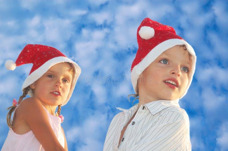 Crianças do Natal de encontro ao céu azul fotografia de stock royalty free