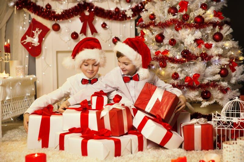 Crianças do Natal que abrem a caixa de presente atual, árvore do Xmas das crianças fotos de stock