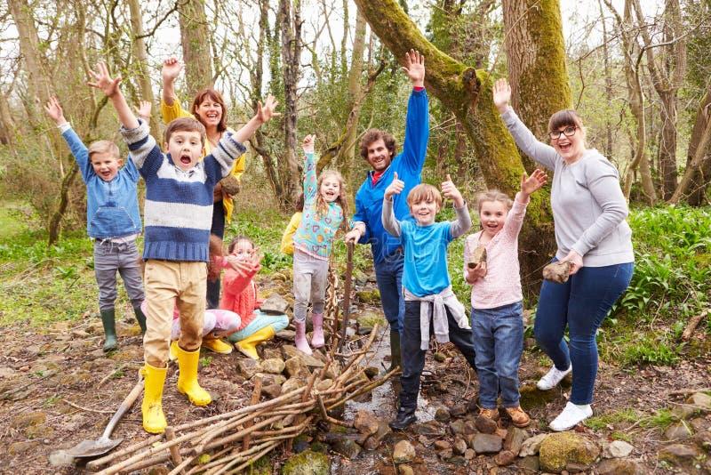 Crianças e adultos que realizam o trabalho da conservação no córrego fotografia de stock royalty free