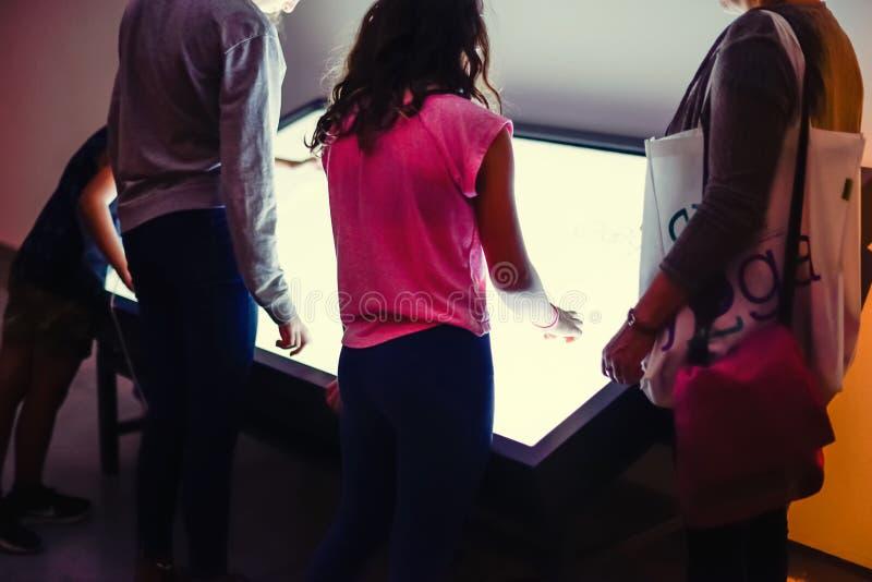 Crianças e adultos que usam o tela táctil interativo em um museu Conceito moderno das tecnologias Foco seletivo fotos de stock