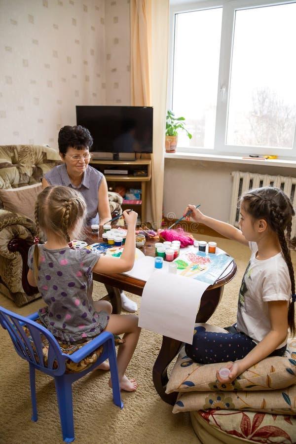 Crianças e avó que pintam em casa, vertical imagens de stock