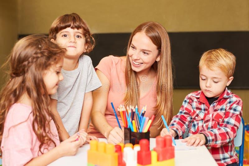 Crianças e educadores se divertem na aula de pintura imagens de stock