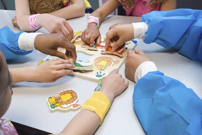 Crianças e enfermeiras que jogam com enigma imagens de stock royalty free
