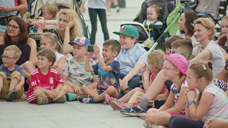 Crianças e mães que olham o desempenho da rua imagens de stock royalty free