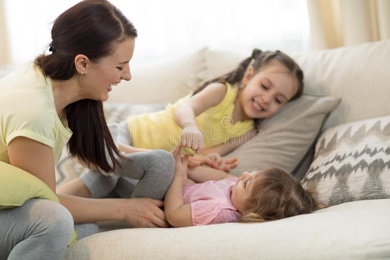Crianças e mamã de sorriso que têm um passatempo do divertimento no sofá na sala de visitas em casa fotografia de stock royalty free