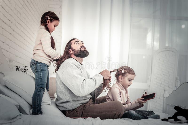 Crianças e pai que jogam um com o otro o cabelo imagem de stock