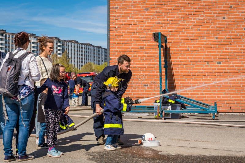 Crianças e pais em um quartel dos bombeiros que tenta uma mangueira de fogo foto de stock