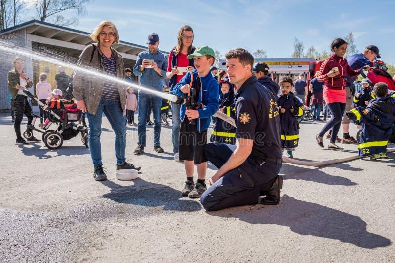 Crianças e pais em um quartel dos bombeiros que tenta uma mangueira de fogo fotografia de stock