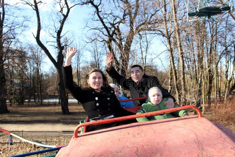 Crianças e pais felizes em um parque de diversões na mola adiantada foto de stock royalty free