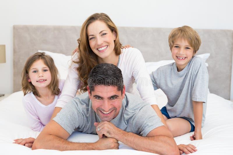 Crianças e pais felizes na cama foto de stock