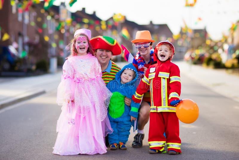 Crianças e pais na doçura ou travessura de Dia das Bruxas fotos de stock royalty free