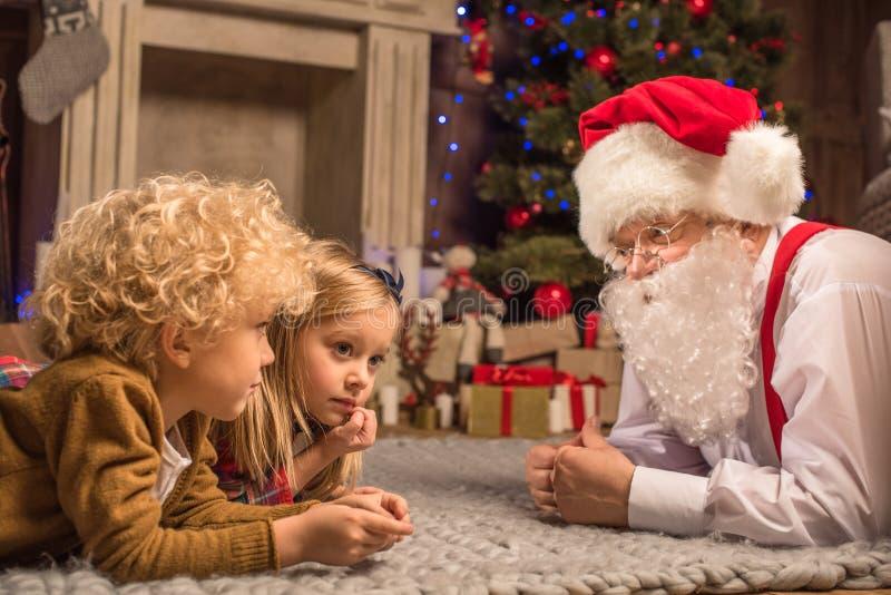Crianças e Santa Claus que encontram-se no tapete fotografia de stock