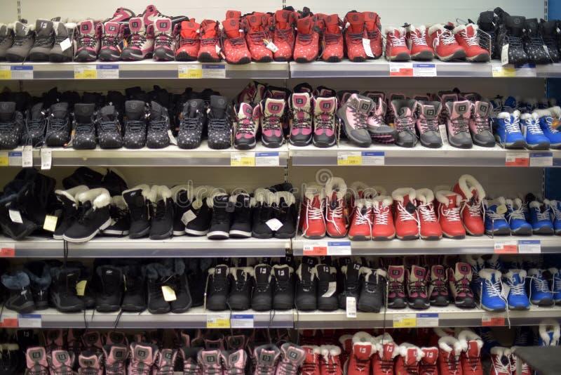 Crianças e sapatas adolescentes do inverno em um supermercado fotos de stock