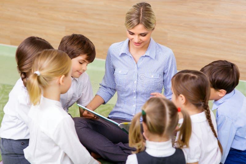 Crianças e seu professor na sessão da leitura fotografia de stock