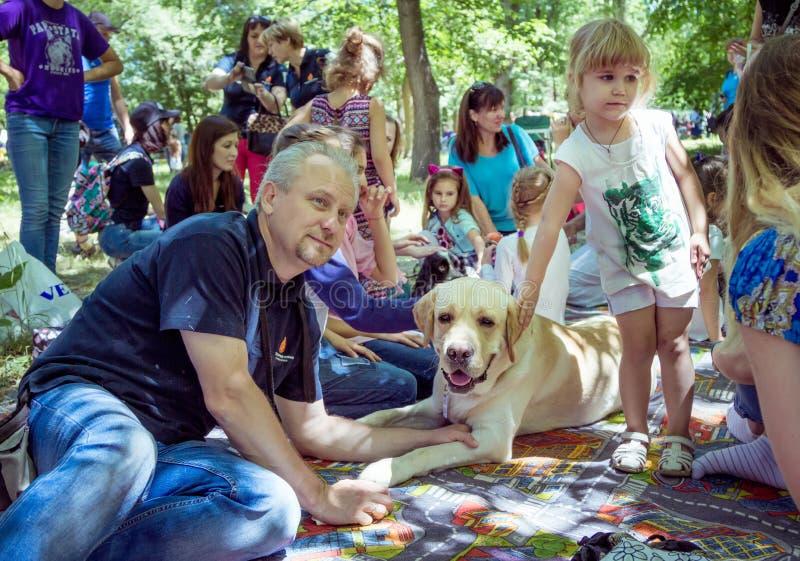 Crianças e seus pais que participam na sessão de terapia do cão imagem de stock